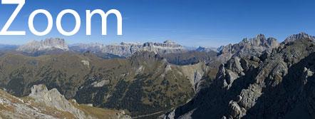 Hoch auflösendes Zoom-Foto: Bergwelt der Dolomiten rund um den Costabella-Kamm. Ausblick auf Latemar, Rosengarten, Langkofel, Stellastock mit Piz Boè, Heiligkreuzkoffel Gruppe, Marmolada, Pale di San Martino