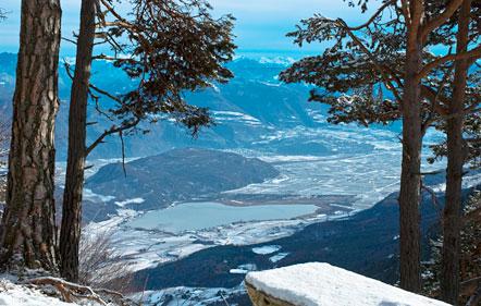 Wandern Südtirol: Schneeschuhwanderung vom Mendel Pass zum Penegal: Ausblick auf das Südtiroler Unterland mit dem Kalterer See und der Leuchtenburg.