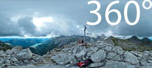 Am Gipfel des Croz dell'Altissimo. Blick auf den Molveno See und die in einer Wolkendecke verhülten Berggipfel der Brenta Dolomiten.