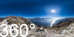 Blick von der Cima Mughera über den Gardasee. Drüben über dem Ostufer des Sees die weißen Gipfel des Monte Altissimo und des Monte Baldo.