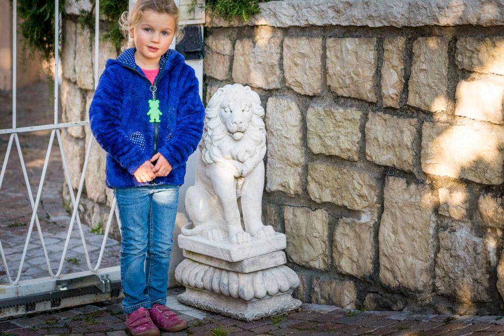 Lisa mit Löwe vor dem verschlossenem Gitte des Parkhotels Kalterer See