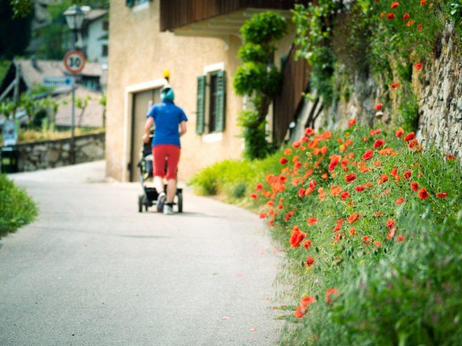 Spaziergängerin mit Kinderwagen und Mohnblumen