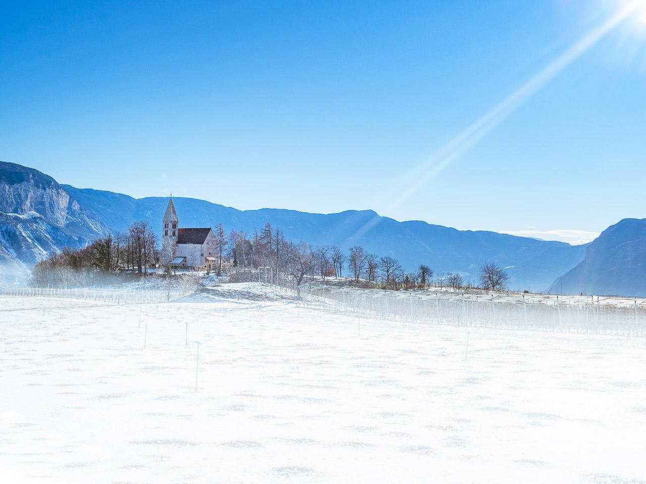 Sonnenstrahl auf die Kirche zum Heiligen Georg in Graun - Winter in Kurtatsch/Südtirol