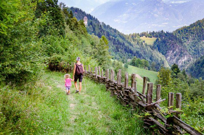 Entlang eines Naturzaun mit Blick auf den Bergfried auf Schloss Eschenlohe