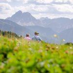 Seniorenpärchen auf der Alm blickt zum Peitlerkofel