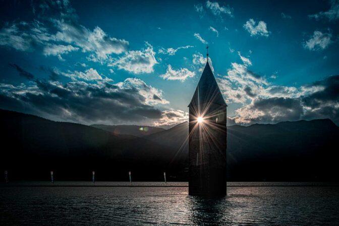 Sonnenuntergang am Reschensee. Die letzten Strahlen fallen durch den Glockenstuhl des versunkenen Kirchturms.